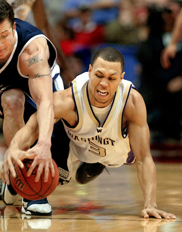 2006 P-I Sports Star of the Year UW's Brandon Roy dives for a loose ball and takes it away from Utah State's David Pak as the University of Washington beat Utah State in the first round of the 2006 NCAA Men's Basketball in San Deigo. (Scott Eklund/Seattle Post-Intelligencer)