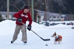 Fido gets into the action during an outdoor hockey game in Field, B.C. (Photo by Andy Rogers/Red Box Pictures)