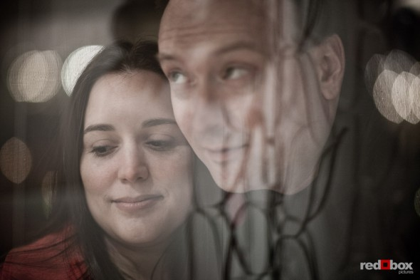 Tara and Brian peer into a shop window in old Ballard during their engagement session. (Photography by Andy Rogers/Red Box Pictures)