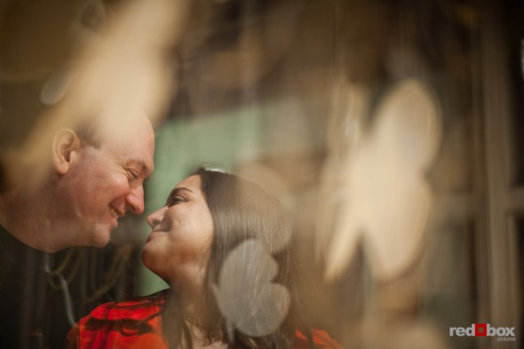 Ballard engagement photos of Tara and Brian next to a storefront window. (Photography by Andy Rogers/Red Box Pictures)