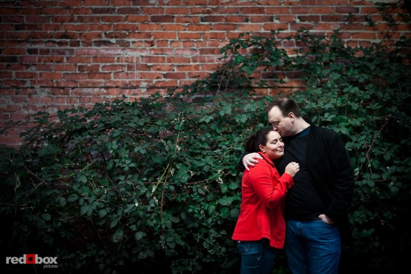 Tara and Brian during their Old Ballard engagement portrait by a brick wall covered in ivy. (Photography by Andy Rogers/Red Box Pictures)