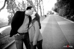 Tara and Brian kiss while walking at the Ballard Locks during their engagement session. (Photography by Andy Rogers/Red Box Pictures)