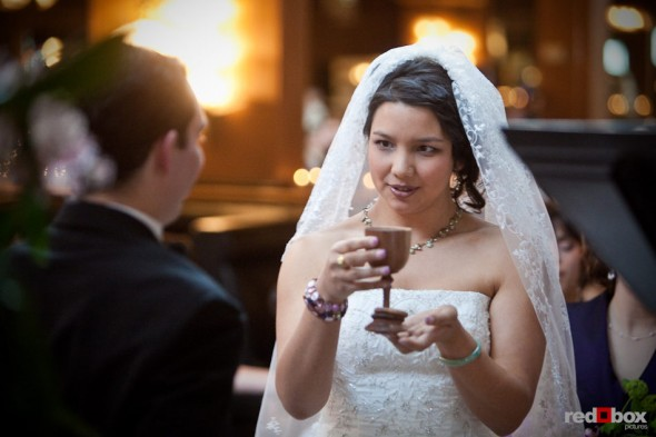 Sarah takes a goblet of wine during her wedding ceremony at the Lake Union Cafe in Seattle. (Photo by Andy Rogers/Red Box Pictures)