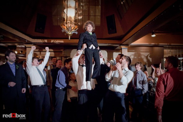 A boy is held aloft for praise after he catches the garter during a wedding at the Lake Union Cafe in Seattle. (Photo by Rob Sumner/Red Box Pictures)