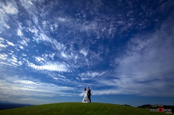 The bride and groom stand atop a hill over looking Seattle and Bellevue from the Golf Club at Newcastle. (Wedding Photography Scott Eklund Red Box Pictures)