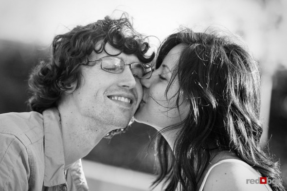 Anghi steals a kiss from Andy during engagement portrait session at Seattle Art Museum Sculpture Park. Photo by Dan DeLong/Red Box Pictures