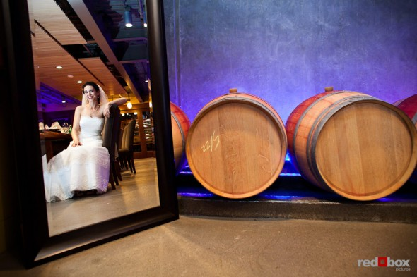 Laura, the bride, is reflected in a mirror just before her wedding to Nathan at the Novelty Hill Januik Winery in Woodinville, WA. (Photo by Dan DeLong/Red Box Pictures)