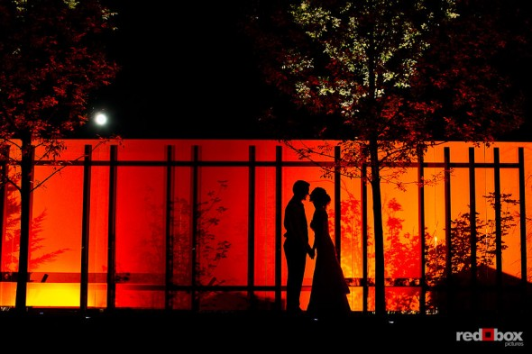 Laura and Nathan kiss with the moon above them during their wedding the Novelty Hill Januik Winery in Woodinville, WA. (Photo by Dan DeLong/Red Box Pictures)