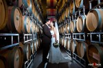 Laura and Nathan steal a kiss among the wine barrels during their wedding reception at the Novelty Hill Januik Winery in Woodinville, WA. (Photo by Dan DeLong/Red Box Pictures)
