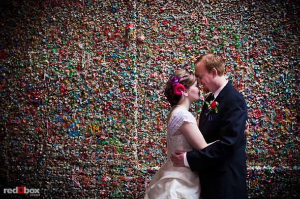 Maureen and Alex kiss by the gum wall in Post Alley at the Pike Place Market prio to their wedding at the Georgetown Ballroom in Seattle. (Photo by Andy Rogers/Red Box Pictures)