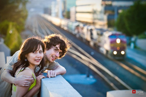 Anghi and Andy watch a freight train during their engagement portrait session in Seattle. Photo by Dan DeLong/Red Box Pictures