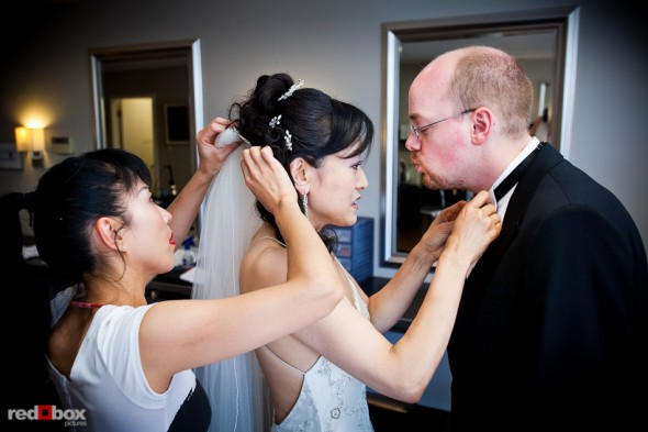 Nobuyo has finishing touches put on her hair as she fixes Rory's bow tie at Adore in Seattle prior to their Virginia V wedding. Photo by Seattle wedding photographer Andy Rogers of Red Box Pictures.