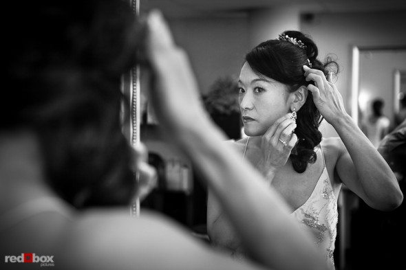 Nobuyo puts on her earrings after having her hair and makeup done at Adore in Seattle prior to her Virginia V wedding. Photo by Seattle wedding photographer Andy Rogers of Red Box Pictures.