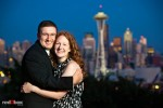 The evening skyline of Seattle is the background for Katherine and Bryan during engagement photo session at Kerry Park. (Photo by Dan DeLong/Red Box Pictures)