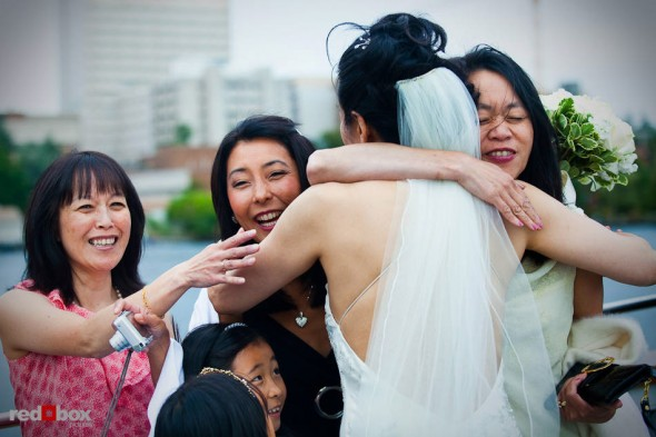 Friends give hugs of congratulations to Nobuyo after she married Rory aboard the Virginia V steamship on Lake Union in Seattle. (Photo by Dan DeLong/Red Box Pictures)