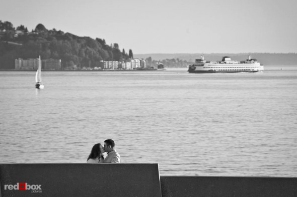 Katherine and Bryan kiss as a ferry sails across Elliott Bay during their engagement photo session at the Olympic Sculpture Park in Seattle. (Photo by Dan DeLong/Red Box Pictures)