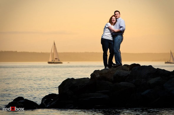 The sun sets over Puget Sound behind Katherine and Bryan during their engagement session at Myrtle Edwards Park in Seattle. (Photo by Dan DeLong/Red Box Pictures)