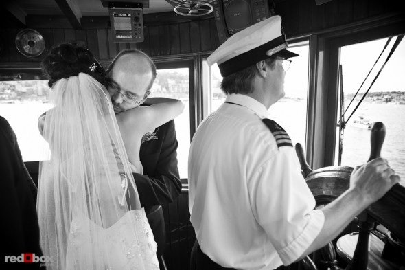 Nobuyo and Rory embrace in the pilot house following their wedding ceremony aboard the Virginia V on Lake Union in Seattle. Photo by Seattle wedding photographer Andy Rogers of Red Box Pictures.