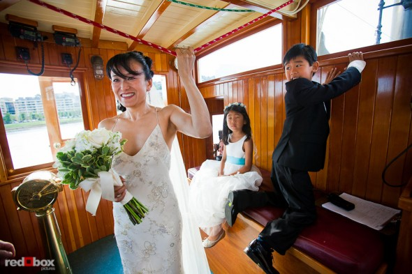 Nobuyo pulls the rope to trigger the Virginia V's steam whistle as the ship disembarks prior to her wedding ceremony and recpetion. Photo by Seattle wedding photographer Andy Rogers of Red Box Pictures.