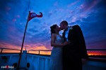 Nobuyo and Rory kiss at the blow of the Virginia V steam ship during their wedding reception on Lake Washington in Seattle. Photo by Seattle wedding photographer Andy Rogers of Red Box Pictures.