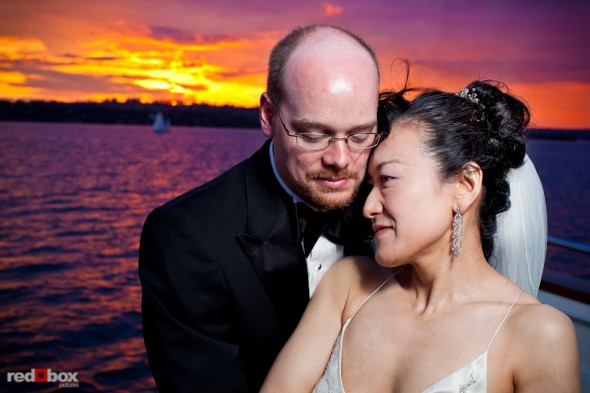 Nobuyo and Rory enjoy a beautiful sunset on Lake Washington during their wedding reception aboard the Virginia V in Seattle. Photo by Seattle wedding photographer Andy Rogers of Red Box Pictures.