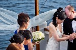 Nobuyo and Rory bow their heads in prayer during their wedding ceremony aboard the Virginia V on Lake Union in Seattle. Photo by Seattle wedding photographer Andy Rogers of Red Box Pictures.