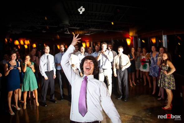 Andy tosses Anghi's garter during their wedding reception at The Canal in Seattle. (Photo by Dan DeLong/Red Box Pictures)