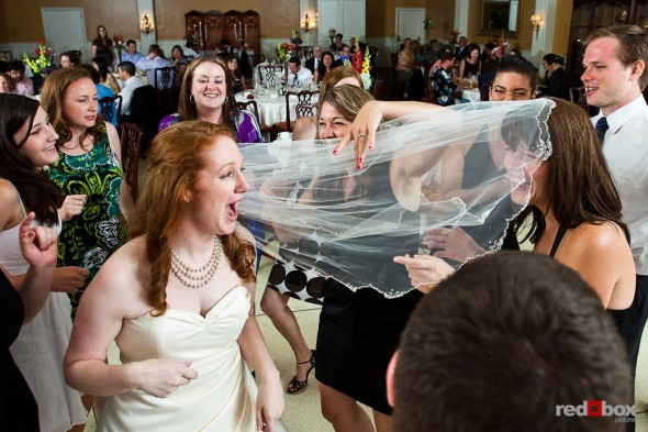 Katherine's veil gets tangled with her sister as they dance with guests during their wedding reception at the Women's University Club in Seattle. (Photo by Dan DeLong/Red Box Pictures)