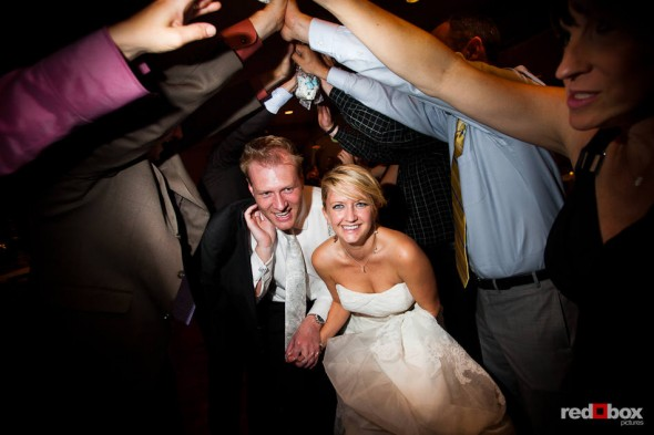 Mike and Angi nearly have to crawl to walk under the arch of arms created by guests during a sendoff to conclude their wedding reception at The Willows Lodge in Woodinville, WA. (Photo by Dan DeLong/Red Box Pictures)