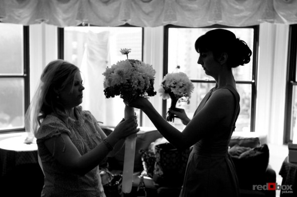 The bride and her bridesmaid work on her bouquet at the Sorrento Hotel before they head to the wedding at The Hall at Fauntleroy in West Seattle, Washington. (Wedding Photography By Scott Eklund Red Box Pictures Seattle)