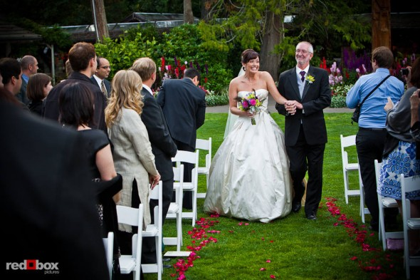Suzy and her father walk down the aisle during her outdoor wedding with Michael at Kiana Lodge in Poulsbo, WA. (Photo by Andy Rogers/Red Box Pictures)