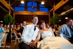 Suzy and Michael enjoy a video of their lives during their wedding reception at Kiana Lodge in Poulsbo, WA. (Photo by Dan DeLong/Red Box Pictures)