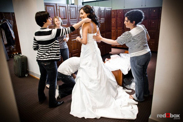 Bride Nadine is helped with her wedding dress in the beautiful facilities at the Plateau Club in Sammamish, WA. (Photo by Dan DeLong/Red Box Pictures)
