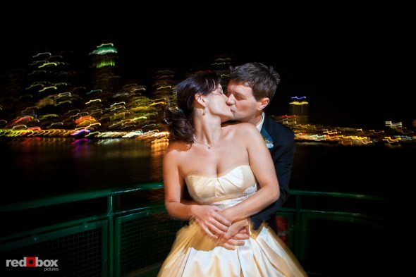 With the Seattle skyline behind them, Suzy and Michael kiss while returning to the city aboard a ferry after their wedding at Kiana Lodge near Bainbridge Island. (Photo by Dan DeLong/Red Box Pictures)