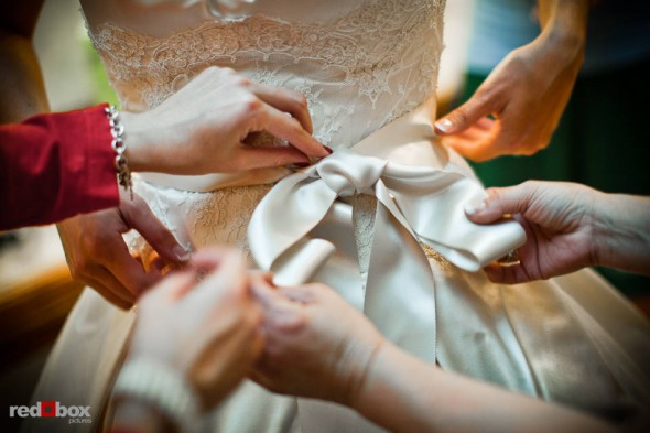 Bridesmaids help Suzy tie the bow of her wedding dress before she and Michael are married at Kiana Lodge in Poulsbo, WA. (Photo by Dan DeLong/Red Box Pictures)