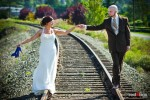 Liz and Ted walk on the railroad tracks near Hidden Meadows in Snohomish, WA before their summer wedding. (Photo by Dan DeLong/Red Box Pictures)