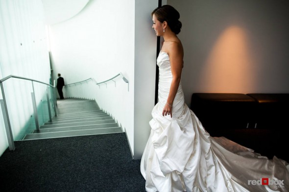 Nora peeks at Neill during their first look before their wedding at the Bellevue Art Museum. (Photo by Dan DeLong/Red Box Pictures)