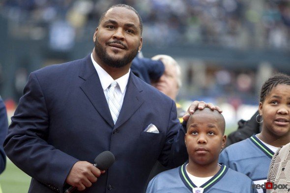Walter Jones, rests his hand on the top of his son's head as they watch as his number is retired during the two-minute warning of the first half as the Seattle Seahawks beat the Carolina Panthers 31-14 at Qwest Field in Seattle. (Seattle Sports Photography By Scott Eklund/Red Box Pictures)
