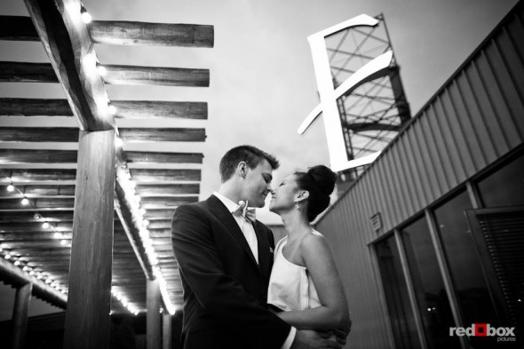 After their wedding ceremony, Jordan and Angie kiss under the giant E sign that's atop the Edgewater Hotel in Seattle. (Photo by Dan DeLong/Red Box Pictures)