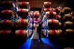 The bride and groom, Michele & Tom, share a kiss in the wine barrel room at Novelty Hill-Januik Winery in Woodinville, Washington. Seattle Wedding Photographer Scott Eklund/Red Box Pictures