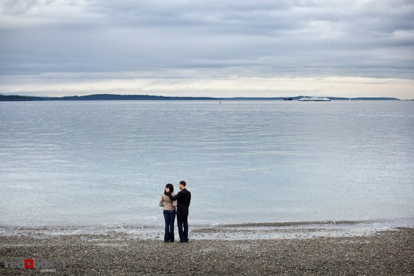 Nick and Tia watch a passing ferry from Alki Beach in West Seattle for their engagement photo session. (Photography by Dan DeLong/Red Box Pictures)