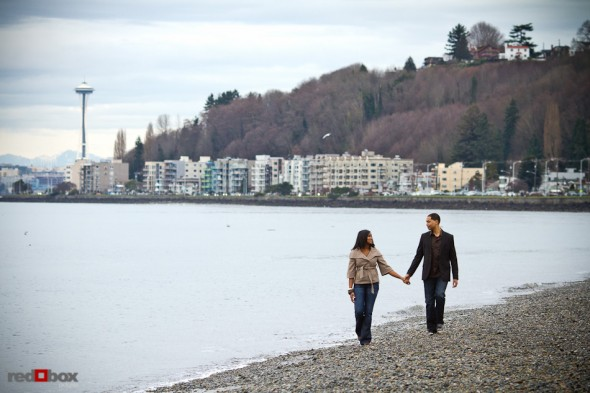 With the space needle in the distance, Nick and Tia walk along Alki Beach in West Seattle for their engagement photo session. (Photography by Andy Rogers/Red Box Pictures)
