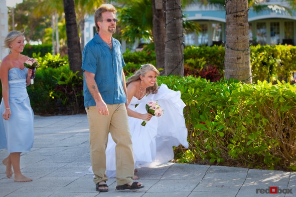 The brides tries to hide from view of her groom as she walks with her father before the wedding at the Old Bay Bahama Resort in the Bahamas. (Wedding Photography by Scott Eklund/Red Box Pictures)