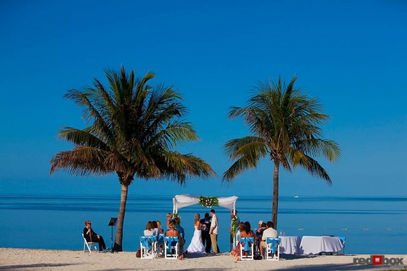 The bride and groom exchange vows under the palm trees during their wedding at the Old Bay Bahama Resort in the Bahamas. (Wedding Photography by Scott Eklund/Red Box Pictures)