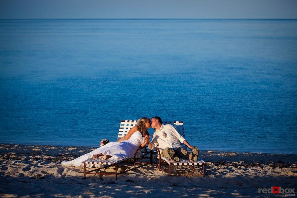The bride and groom share a kiss while relaxing on the beach after their wedding at the Old Bay Bahama Resort in the Bahamas. (Wedding Photography by Scott Eklund/Red Box Pictures)