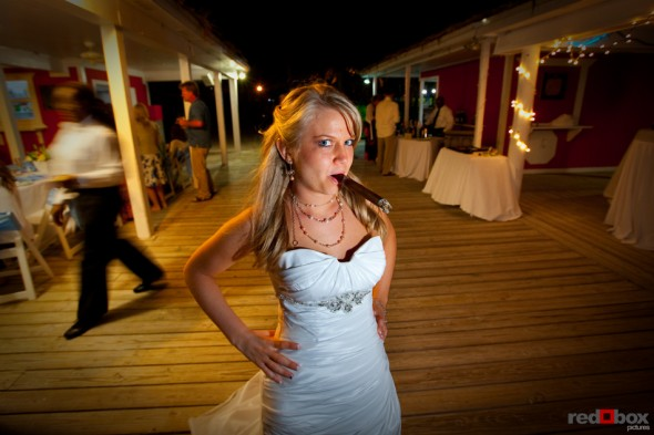 Tasha takes a few puffs on a cigar at her reception at the Old Bahama Bay Resort in the Bahamas. Wedding Photography by Scott Eklund/Red Box Pictures