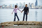 Nick and Tia walk on a large piece of driftwood at Seacrest Park in West Seattle for their engagement photo. (Photography by Andy Rogers/Red Box Pictures)