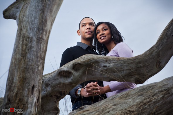 Nick and Tia near driftwood at Seacrest Park in West Seattle for their engagement portrait session. (Photography by Andy Rogers/Red Box Pictures)