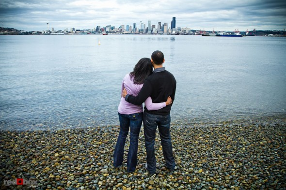 Nick and Tia look out over Elliott Bay and the Seattle skyline from Seacrest Park in West Seattle for their engagement portrait. (Photography by Andy Rogers/Red Box Pictures)
