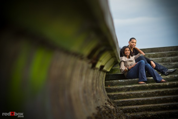 Nick and Tia sit on the stairs to Alki Beach in West Seattle during their engagement photo session. (Photography by Andy Rogers/Red Box Pictures)